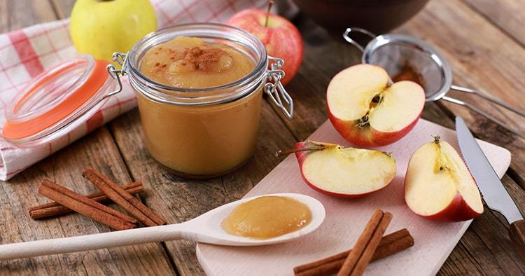 homemade apple jam, apple puree with fresh apples and spices on wooden rustic table