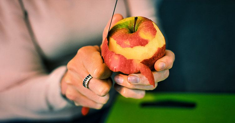 Close-up of hands peeling an apple. Woman's hands removes the skin of a red apple with a knife.