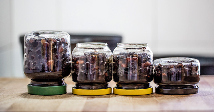 Preserved food in glass jars on wood. Handmade black beans, simmered with sugar and soy sauce.