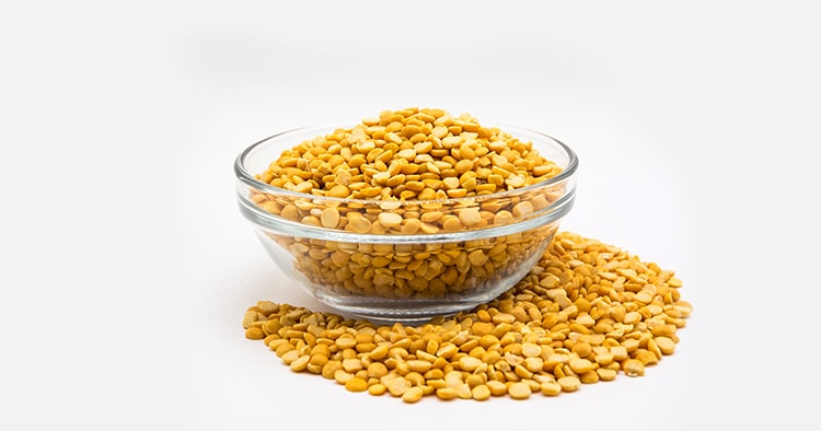 Yellow lentil in glass bowl isolated on white background