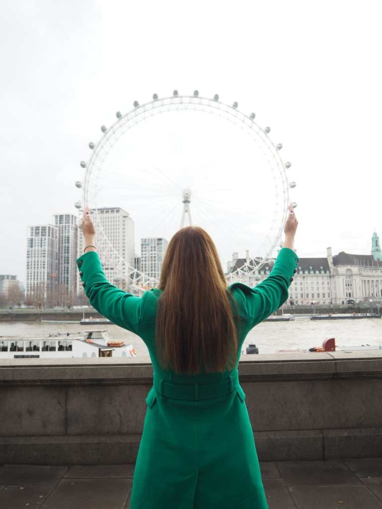 Picture of me standing in front of the london wheel pretending to cup it in my hands.  Six Things I Wish I Knew When I Moved To London.