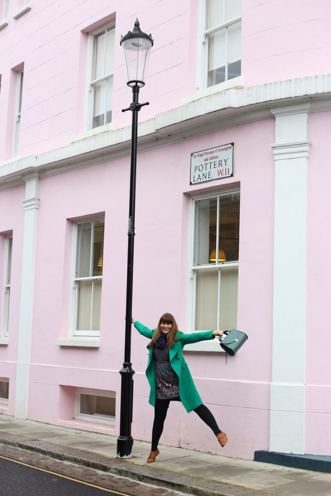 Pretentious Fringe wearing her emerald green coat and having fun swinging off a lamppost