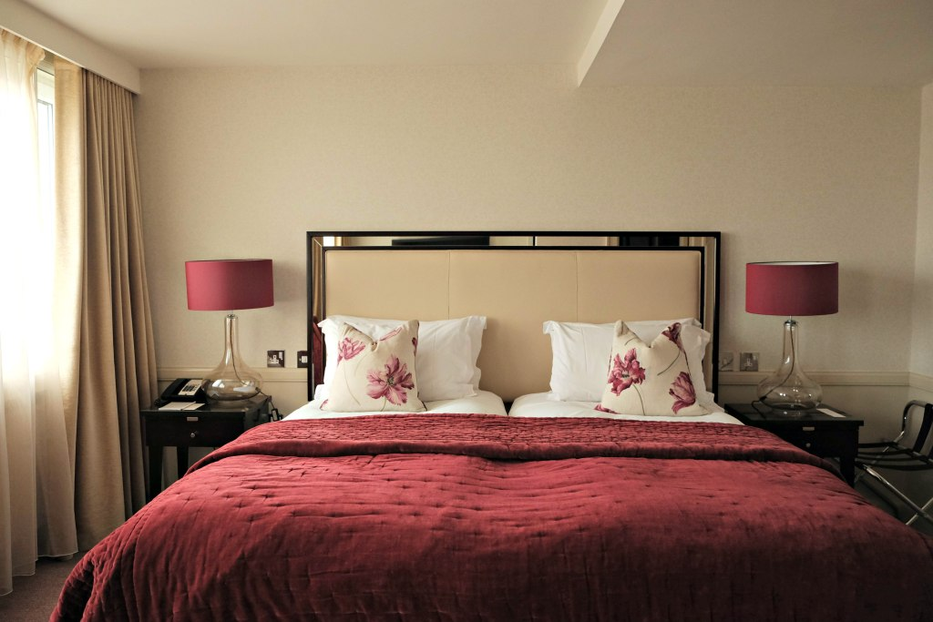 Picture of the room with a beautiful bed, matching red coverlet and bedside lamps.