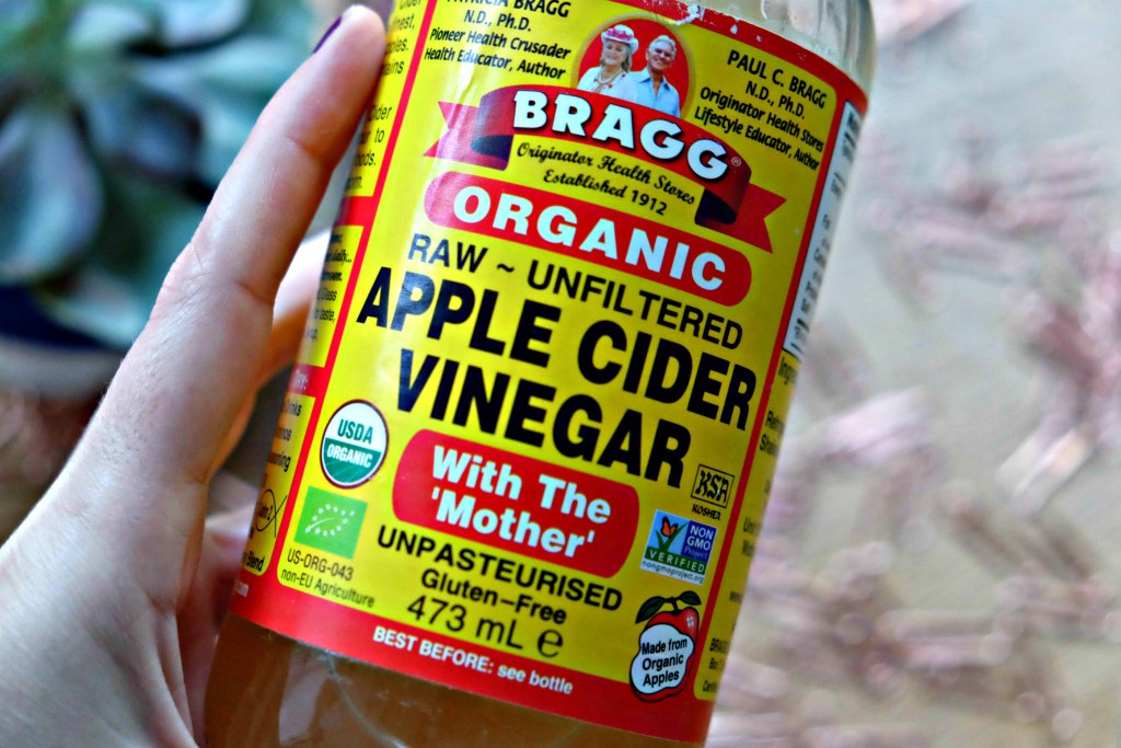 Close up shot of apple cider vinegar bottle with brand and details clear.  Three Ways To Use Bragg Organic Apple Cider Vinegar post.