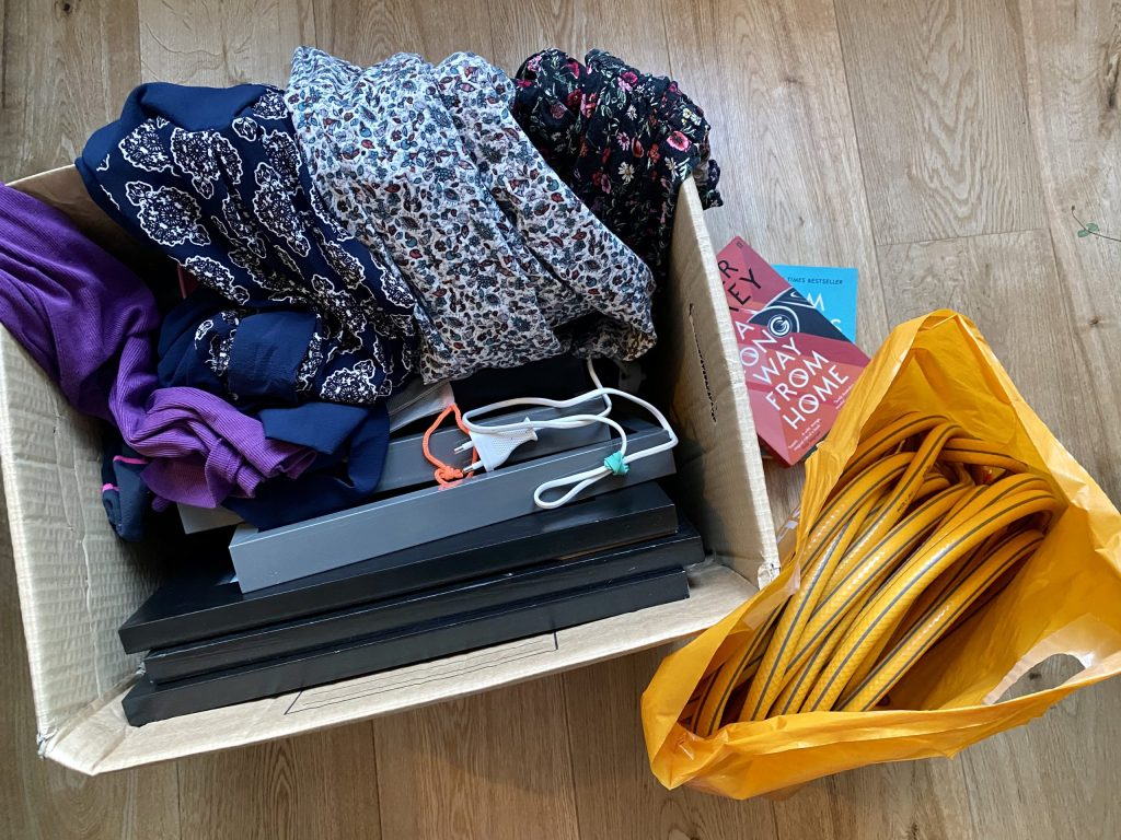 A picture of my donation pile.  Extra clothes, a toothbrush charger and lots of spare frames.  A hose! and some books.  Tackling The Hoarder Room And Your Monica Cupboard.
