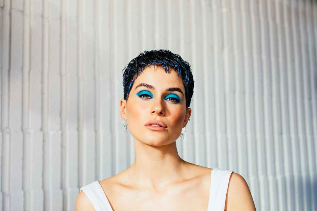 alluring woman with bright makeup against ribbed wall
