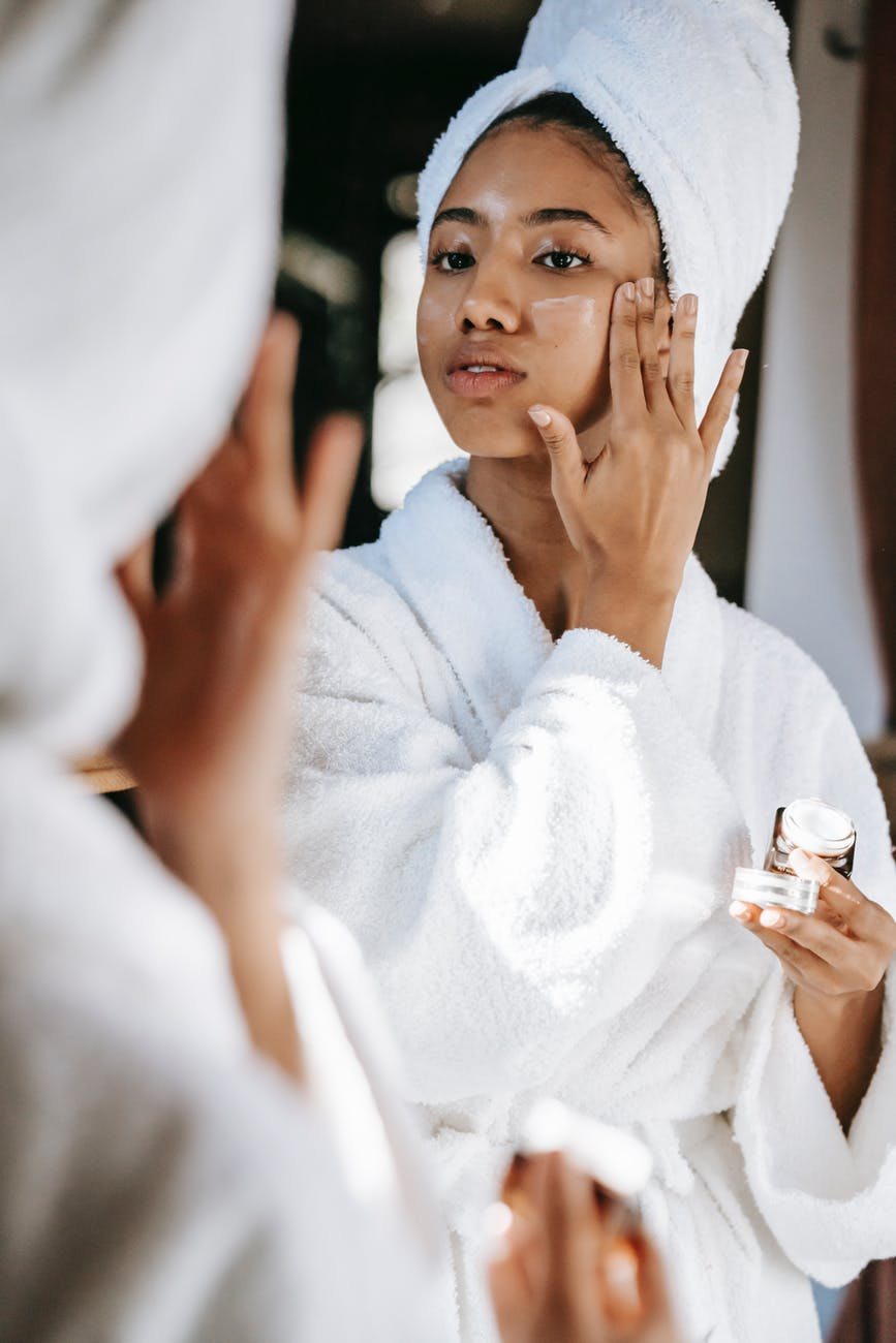 black woman with towel applying cream on face