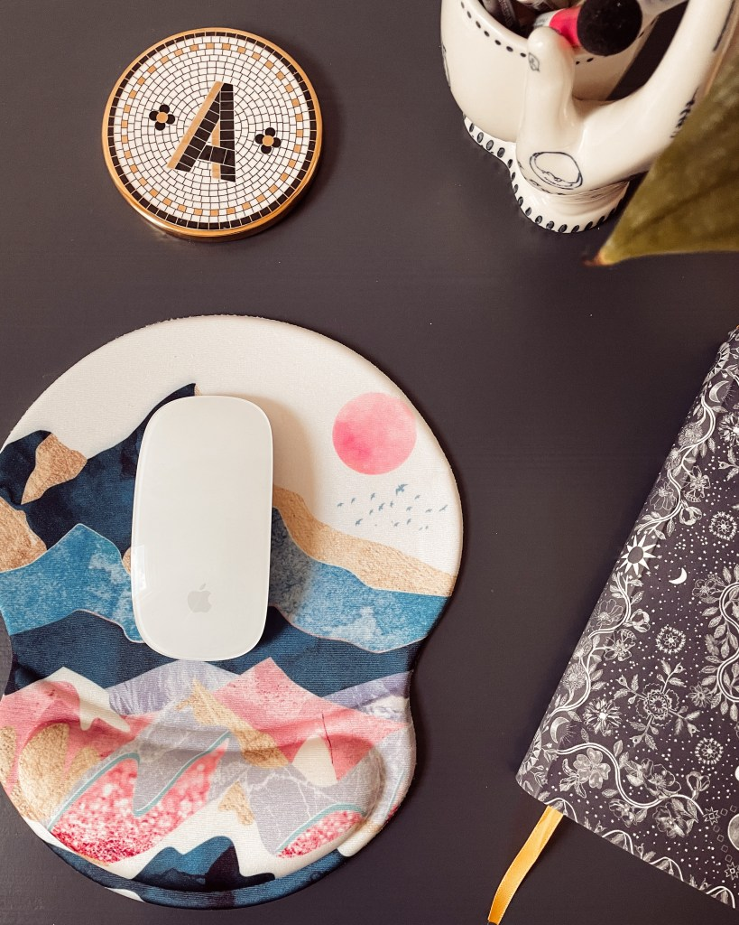 A tiled coaster with an A and a mouse mat with a geometric landscape pattern