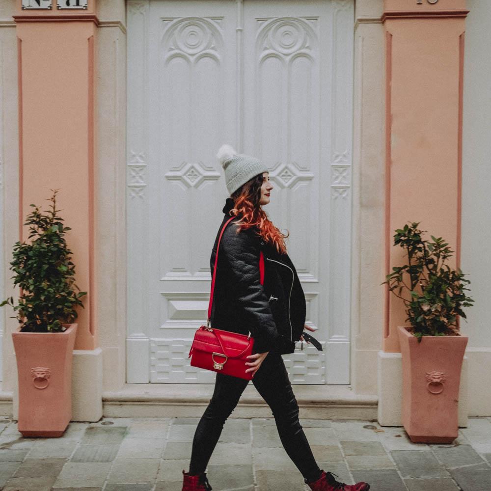 Žena v čiernej leteckej bunde, čiernych džínsoch, červenou kabelkou a so sivou vlnenou čiapkou s brmbolcom na hlave
