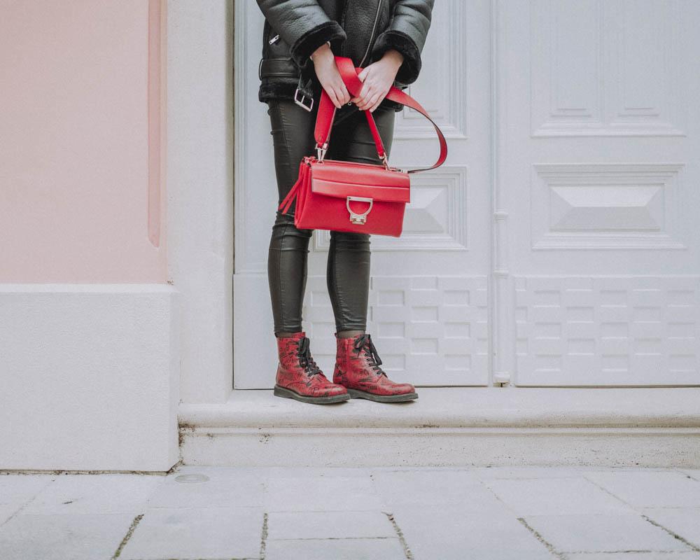 Pohľad na ruky držiace červenú kabelku a nohy v červených topánkach