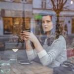 Pohľad cez okno kaviarne na ženu sediacu pri stole s hrnčekom v rukách_1_čo si pozrieť a prečítať počas karantény