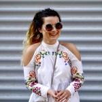 smejuca sa žena v bielych vyšívaných šatách a slnečných okuliaroch