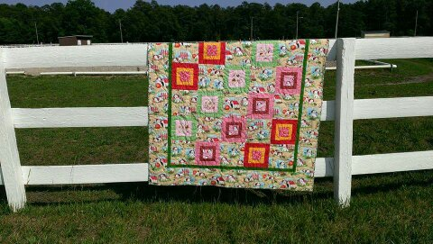 Poky Little Puppy quilt of themed fabric with pink, red, and green accents