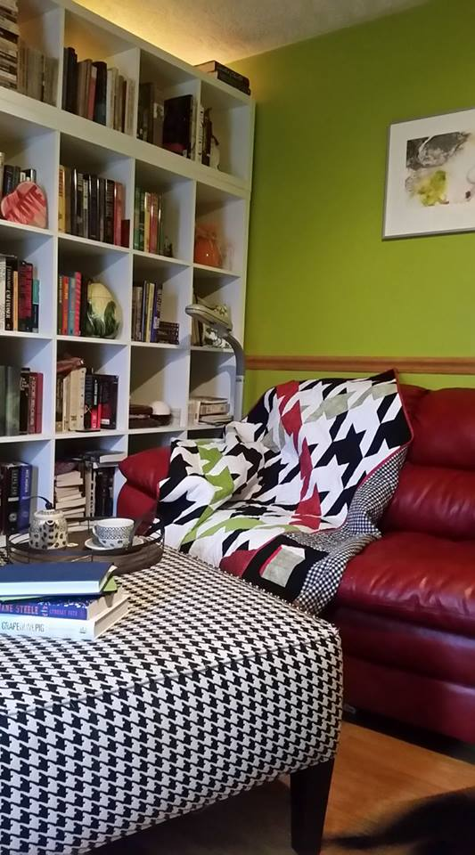Houndstooth quilt made primarily of solid black and white fabrics with stripes of red and green