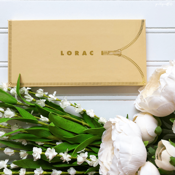 closed lorac unzipped palette on a white background with white flowers