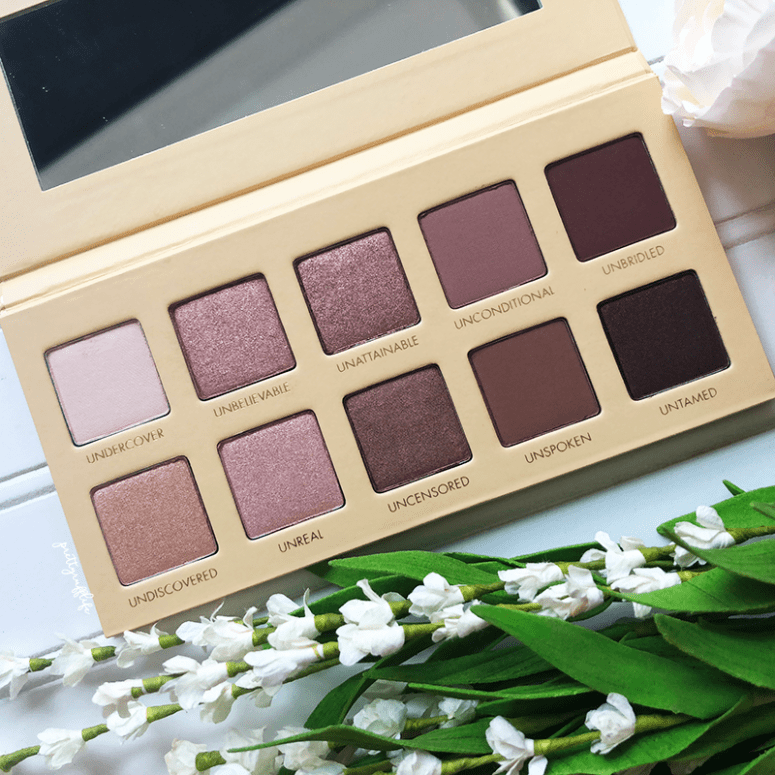closeup of the Lorac Unzipped palette on a white background with white flowers