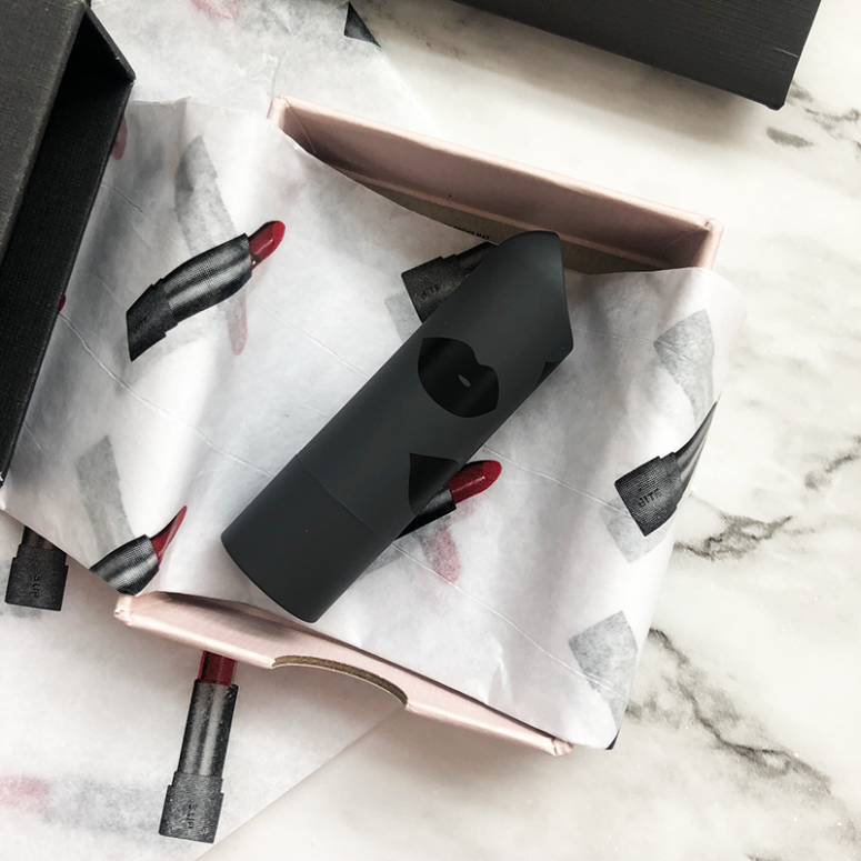 A close up of a Bite Beauty lipstick sitting in a box with lipstick printed tissue paper