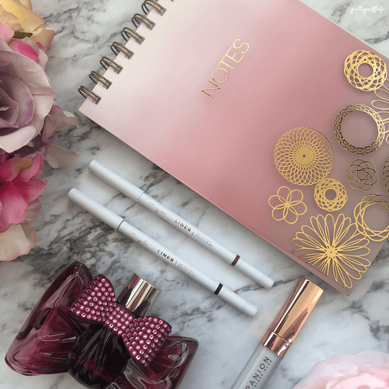 Esqido Pencil Gel Eyeliners on a marble background with a pink notebook, bow shaped bottle of perfume and purple flowers