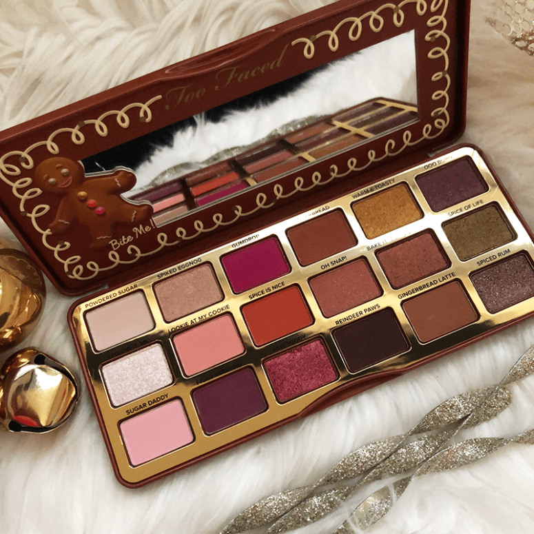 The Too Faced Gingerbread Spice Eyeshadow palette open and sitting on a white fuzzy blanket with gold Christmas ornaments around it