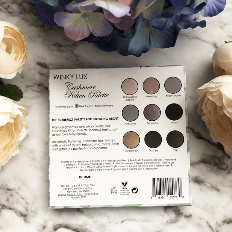 a picture of the back of Winky Lux Cashmere Kitten Palette on a marble background with white and blue flowers in the background