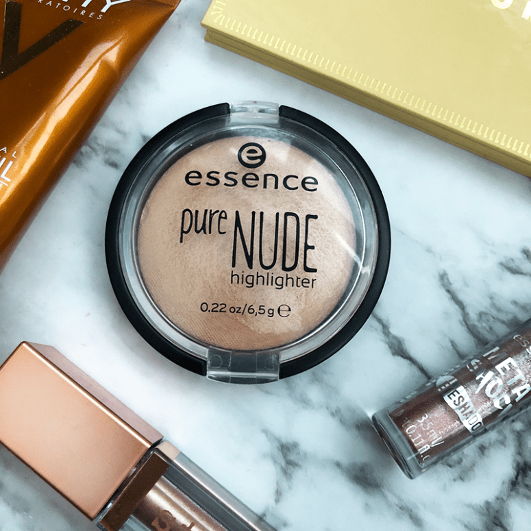 A close up shot of Essence's Pure Nude Highlighter on a white marble background