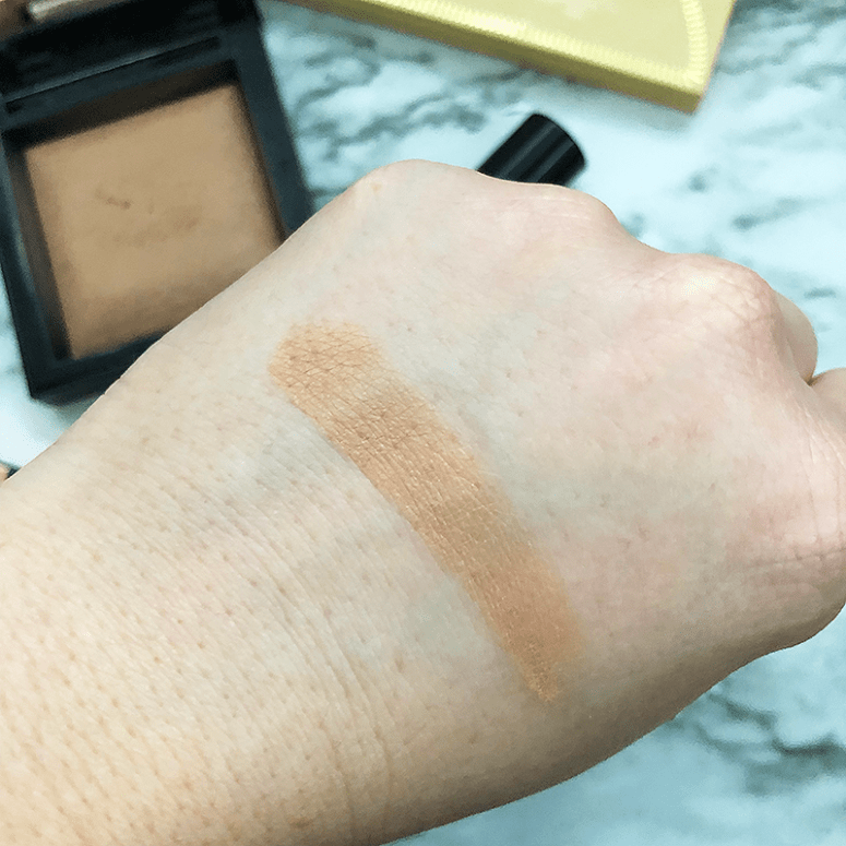 A finger shot of BareMinerals Invisible Bronze packaging on a white marble background