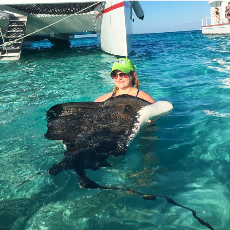 A blonde girl holding a stingray at Stingray City in Grand Cayman Islands