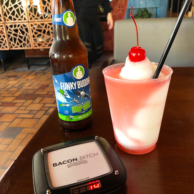 A picture of a slushy cocktail and bottle of Funky Buddah beer on a table at Bacon Bitch in South Beach, Miami