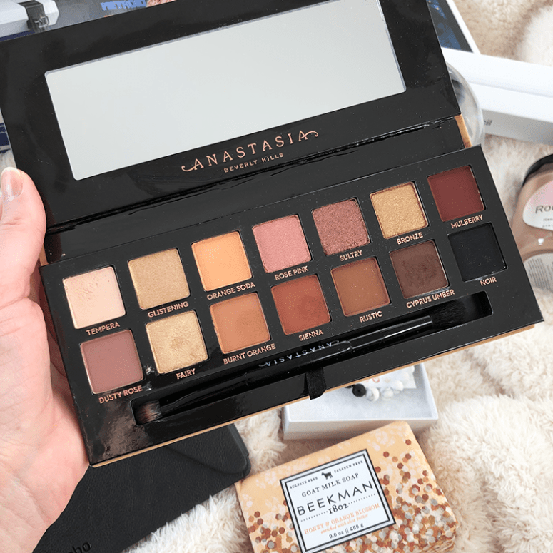 a picture of an open Anastasia Beverly Hills Soft Glam palette with various items in the background