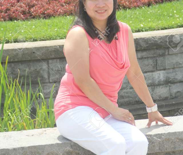 Mature Asian Woman Sitting On A Low Stone Wall Posing For Photos Peach Colored Top
