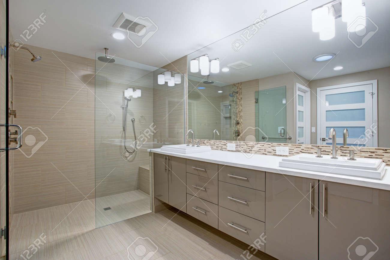 la salle de bains moderne et rafraichissante comprend un lavabo double beige accentue d un dosseret en mosaique sous un miroir de courtoisie place a