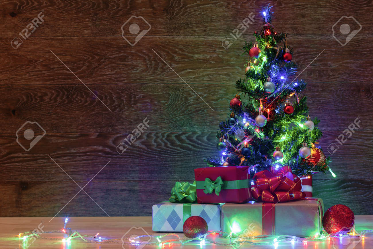 Christmas Tree On A Wooden Background With A Garland And Gifts Stock Photo Picture And Royalty Free Image Image 89606627