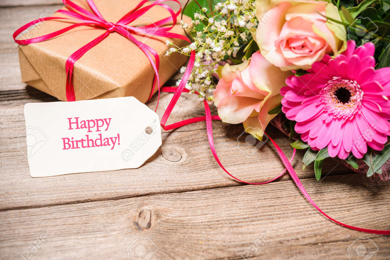 Bunch Of Flowers And Tag With Text On Wooden Background  Happy     Bunch of flowers and tag with text on wooden background  Happy Birthday  Stock Photo