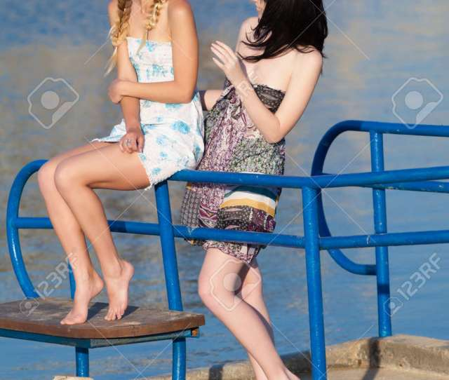Stock Photo Young Women On Background Of Water Two Barefoot Girls In Sundresses Talking On Pier