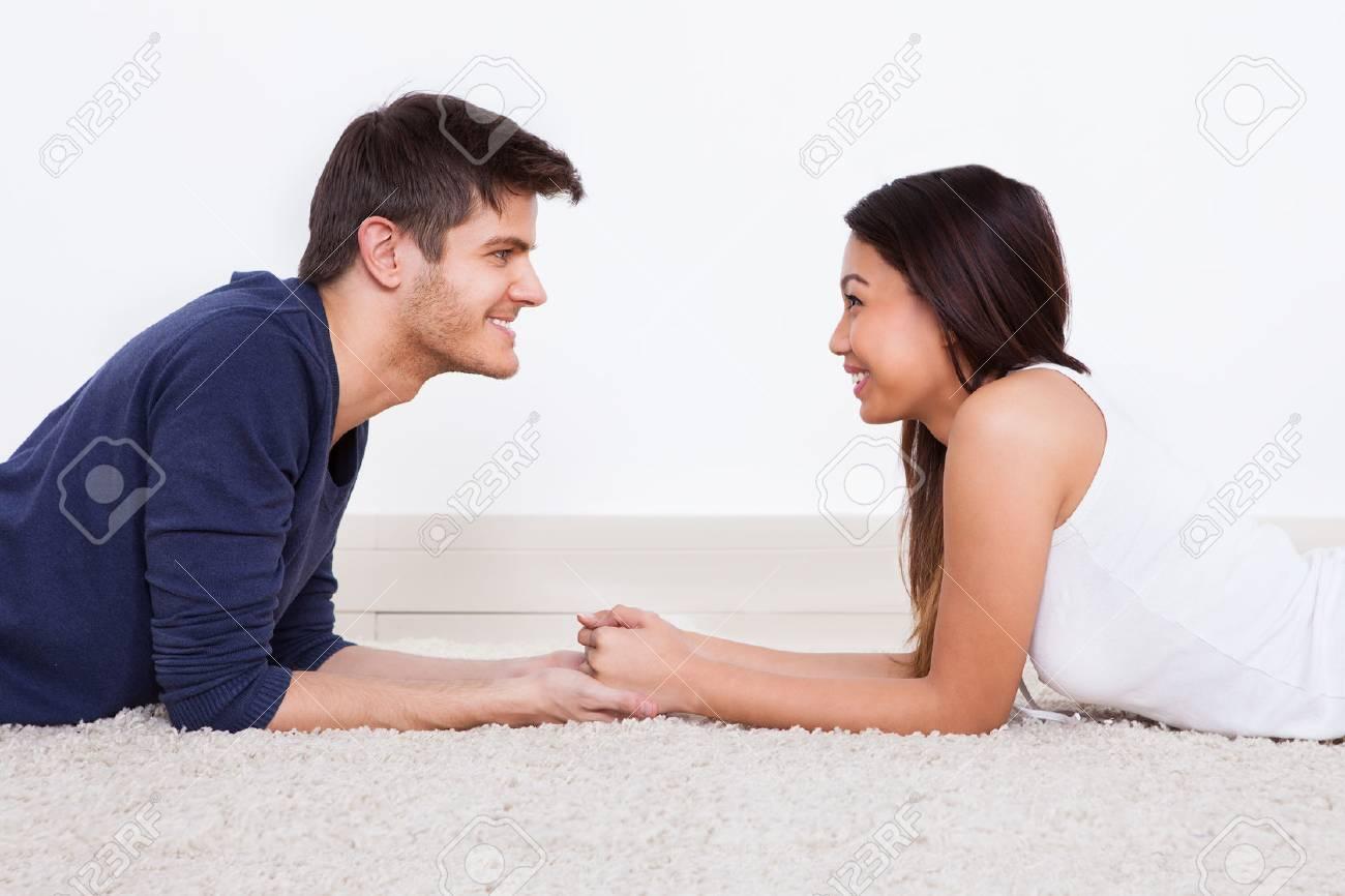 vue de cote de l amour jeune couple a se regarder en position couchee sur le tapis a la maison