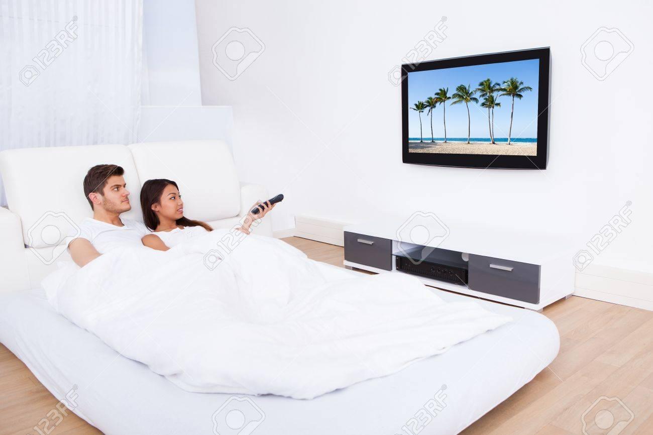 jeune couple de regarder la television tout en se situant dans le lit a la maison banque d images et photos libres de droits image 27242137