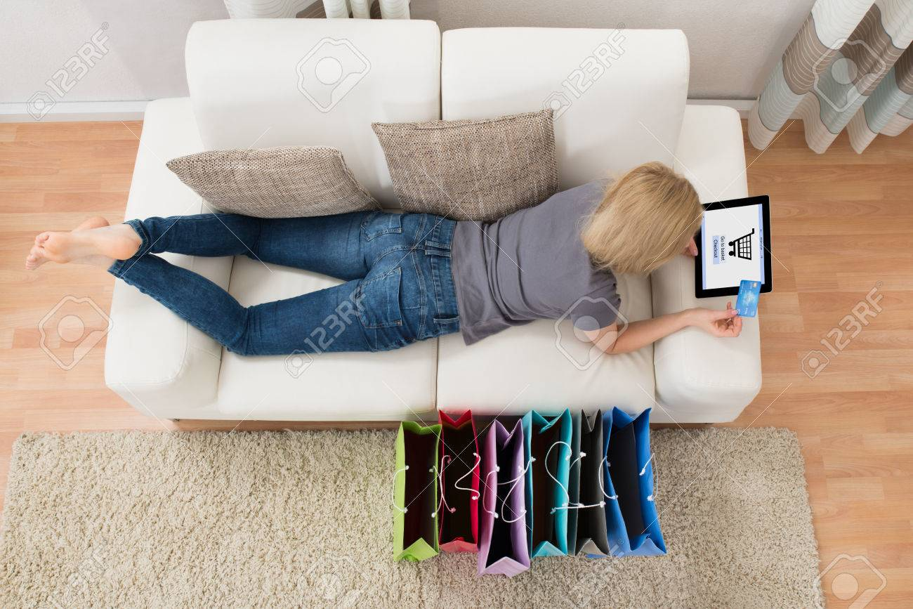 banque d images jeune femme couchee sur canape shopping en ligne sur tablette numerique avec carte de credit a la maison