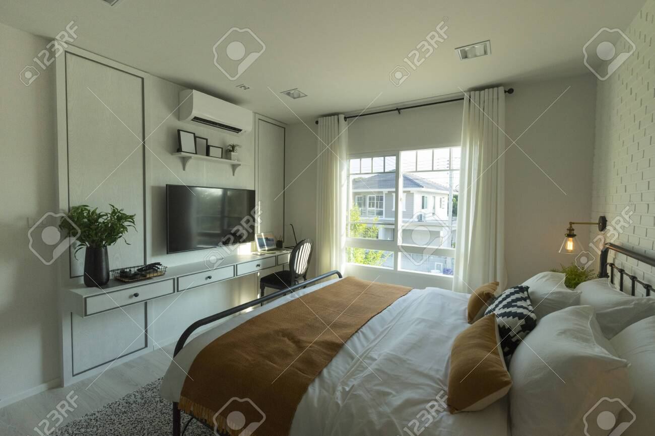 interior of master bedroom with large window and big tv on the