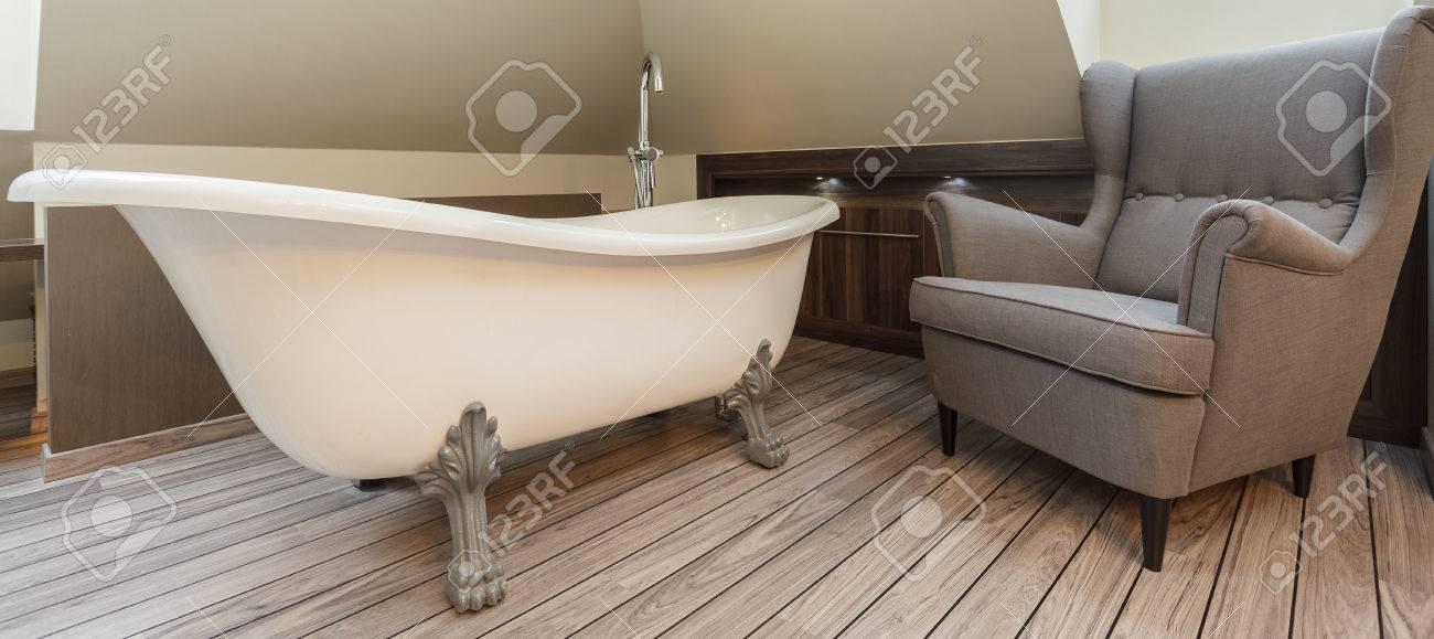salle de bains avec baignoire elegante et confortable fauteuil
