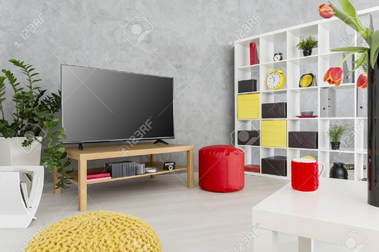 salon contemporain spacieux avec mur en stuc gris et une grande television au milieu