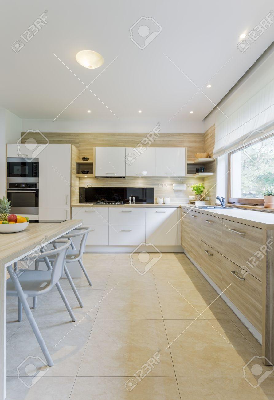 beige et blanc decor de cuisine avec carrelage au sol armoires blanches et commode en bois