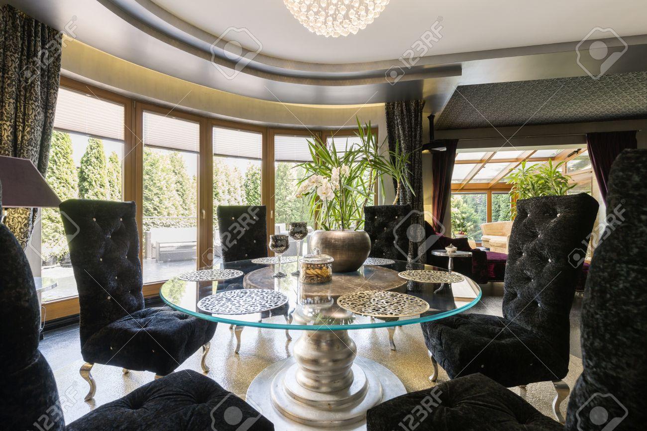 luxueuse salle a manger avec table ronde en verre et des chaises en velours noir