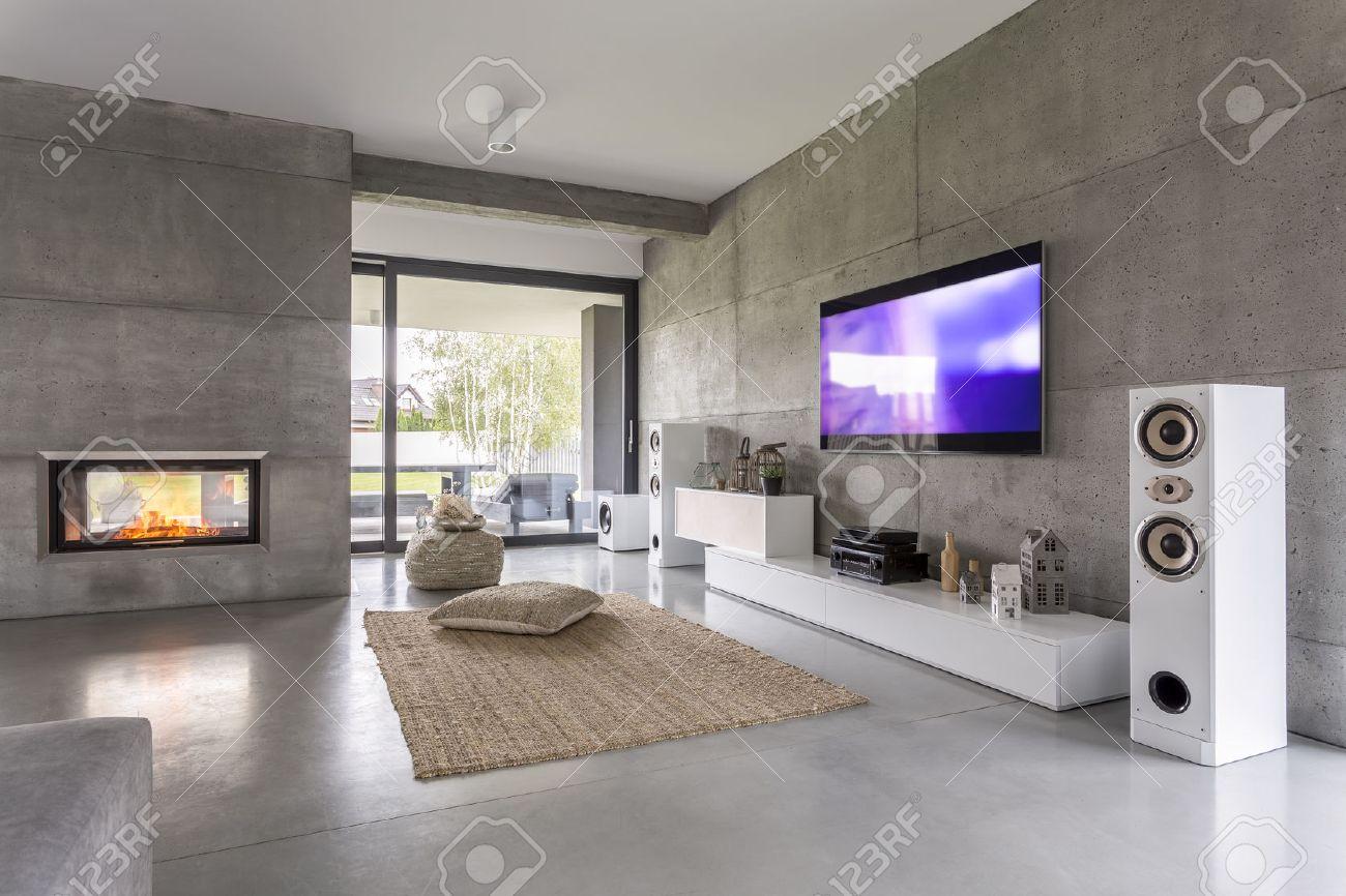 tv salon avec fenetre cheminee et effet de mur de beton