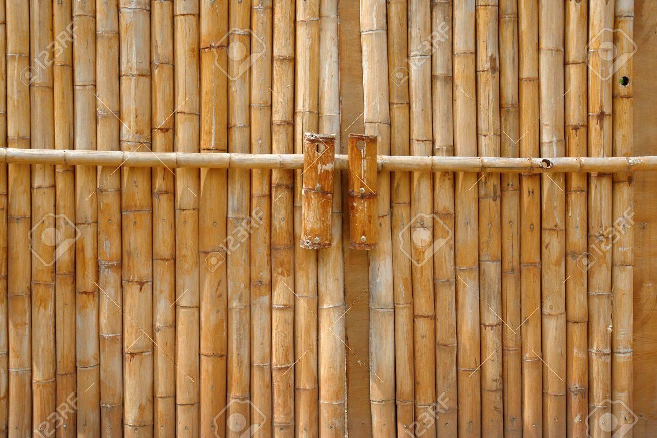 massives portes bambou jaune fermee avec une tige de bambou
