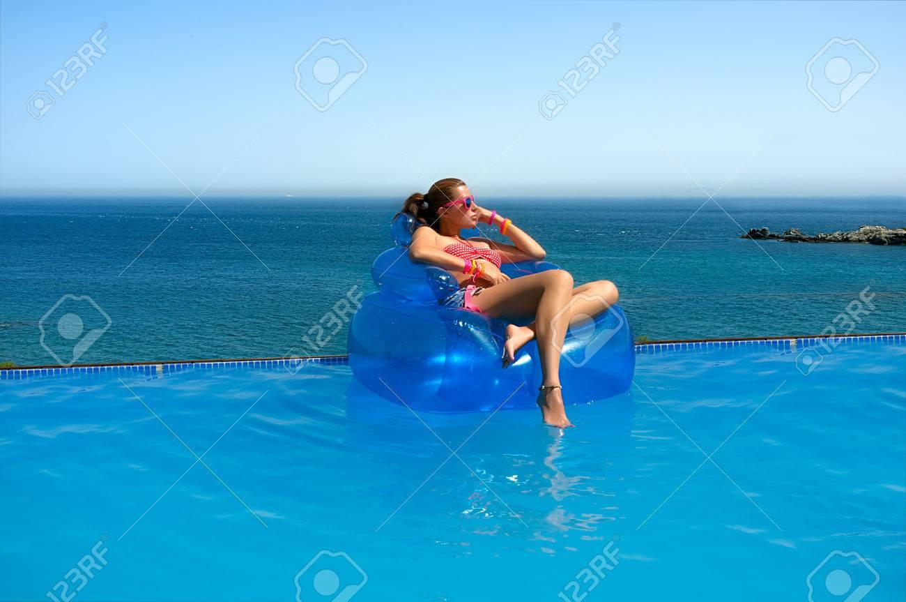 belle jeune femme assise sur la chaise gonflable soleil detendez vous dans la piscine avec vue sur la mer magnifique banque d images et photos libres de droits image 22737073