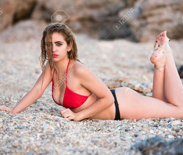 Foto De Archivo Mujer Con Cuerpo Espectacular En Bikini Tanga En Decubito Prono Sobre La Playa Rocosa Levantando Sus Piernas Y Parte Superior Del Cuerpo