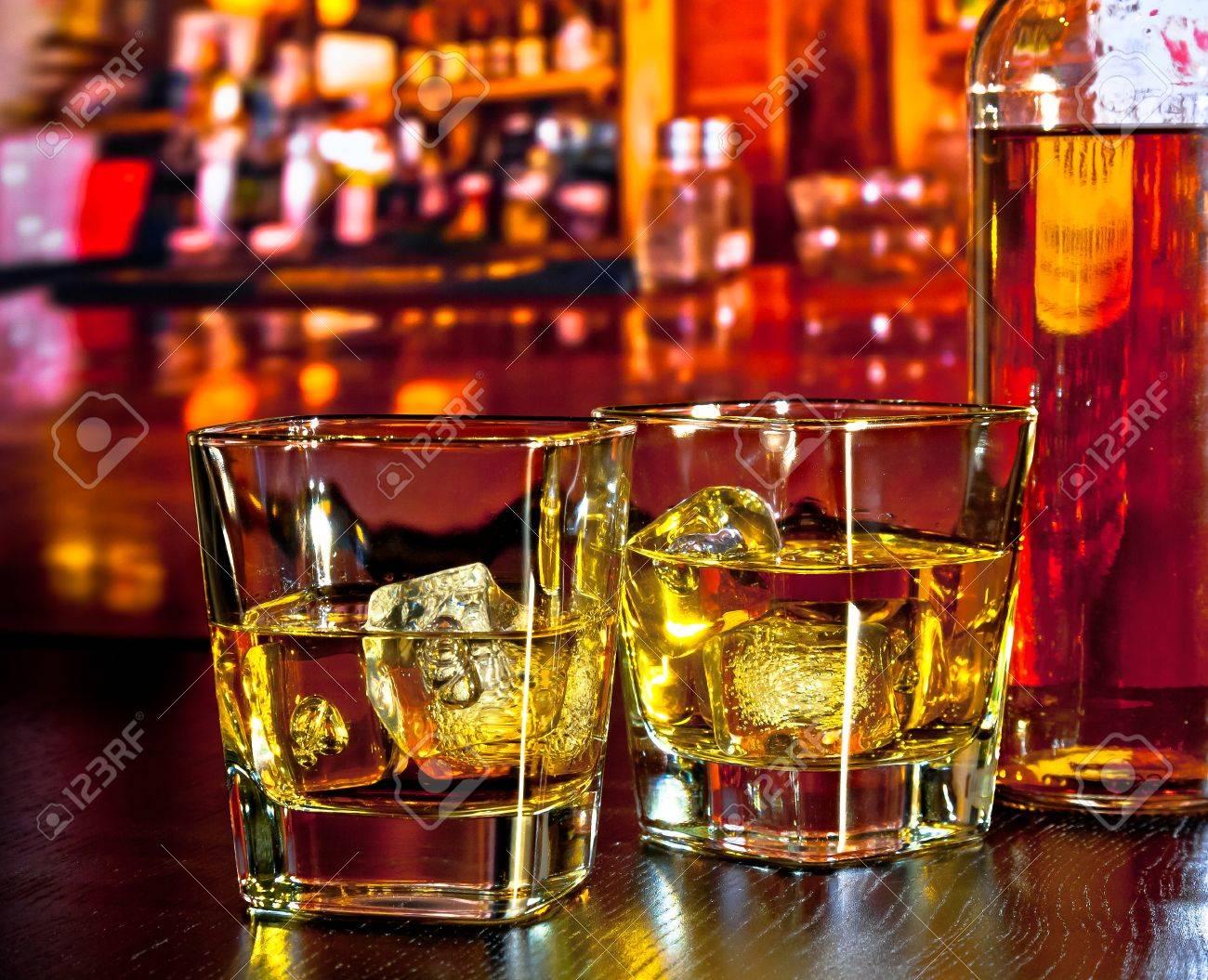 verres de whisky avec de la glace sur la table de bar pres de la bouteille de whisky sur atmosphere chaleureuse bar salon notion