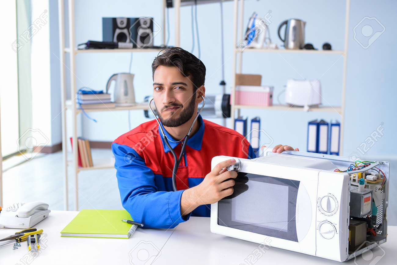 young repairman fixing and repairing microwave oven stock photo picture and royalty free image image 94224854