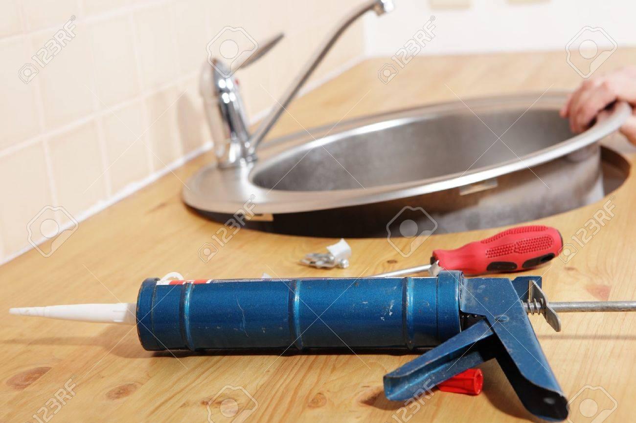 caulking gun with silicone sealant against kitchen sink installation