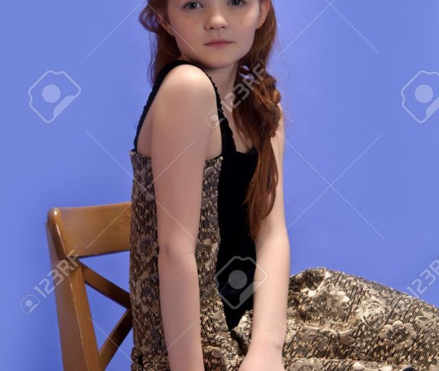 Red Haired Girl Sitting On A High Chair Stock Photo